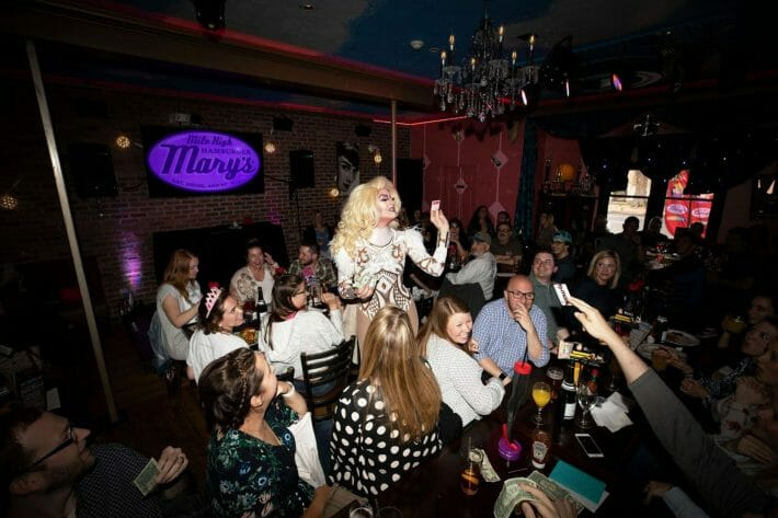 A drag queen stands in the middle of a crowded restaurant performing and receiving tips from the patrons