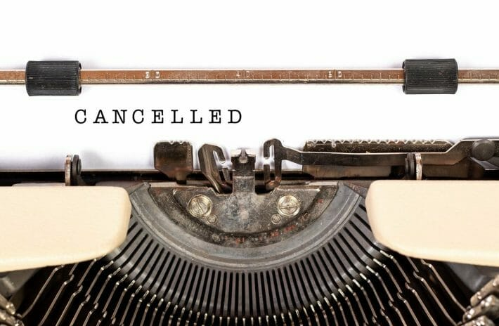 """Funny travel stories - a typewriter has written the word """"cancelled"""" on a white sheet of paper"""