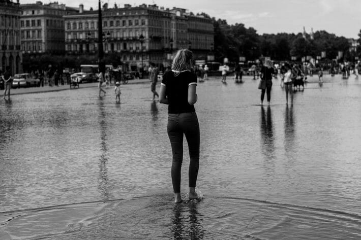 Funny travel stories - Black and white pictures of a slender girl wading through a flooded street