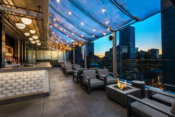 An empty rooftop bar with seating, twinkle lights overhead, and downtown Denver in the background