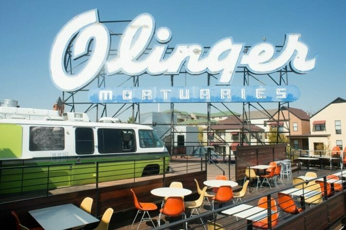 """A large sign reading """"Olinger Mortuaries"""" sits atop one of the best rooftop bars in denver"""