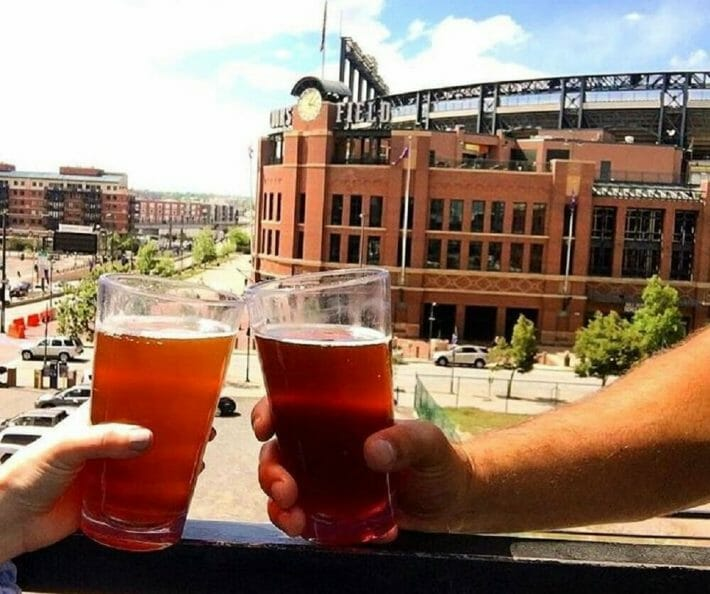 Two pints of beer are clinked together with Coors Field in the background