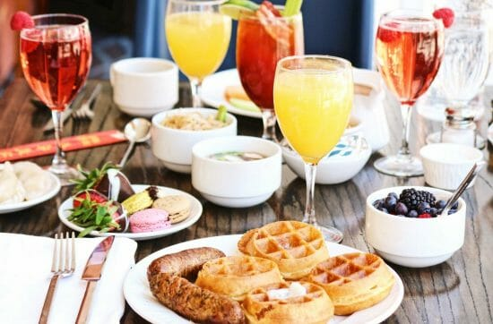 brunch table set with waffles sausage and mimosas