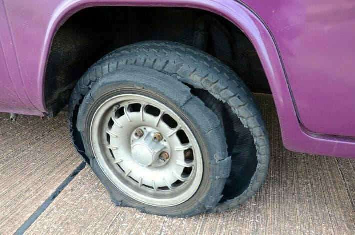 Closeup of a tire blowout on a purple vehicle