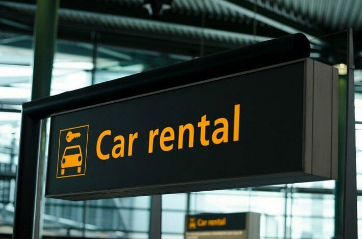 """Black sign at an airport with """"car rental"""" in yellow text"""