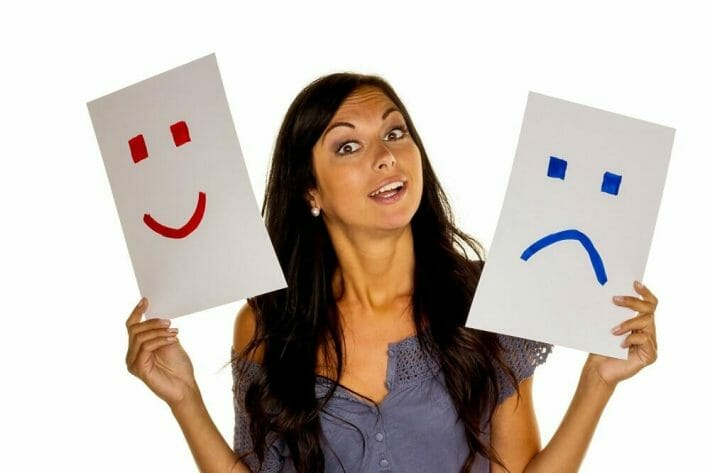 Funny travel stories europe - a woman holds up two sheets of paper, one with a smiling face, and the other with a frowning face