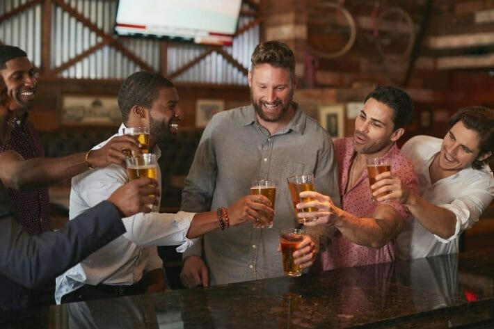 Group Of Male Friends On Night Out For Bachelor Party In Denver In Bar Making Toast Together