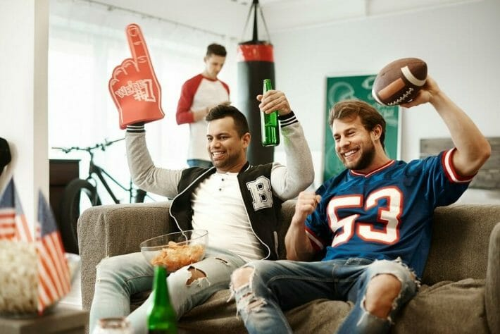 Two male football fans cheer sitting on a couch