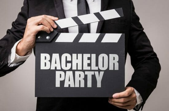 bachelor party in denver - man wearing a suit holding a bachelor party sign