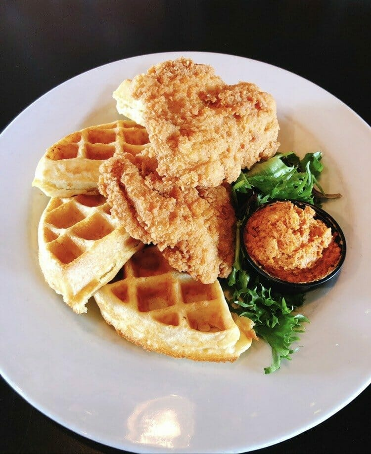 A white plate stacked with fried chicken and waffles