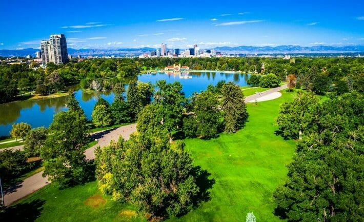 Green parkland, trees, and lake of City Park in Denver. Downtown skyline in the background.