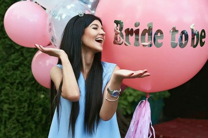 a bride-to-be poses with pink and white balloons for her denver bachelorette party