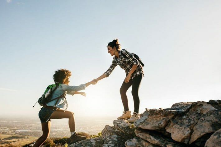 Young woman helping friend climb up a rock; two young females hiking in nature