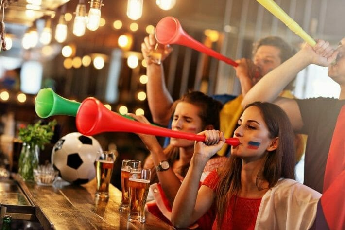 A group of friends watch soccer in a pub, beers on the bar