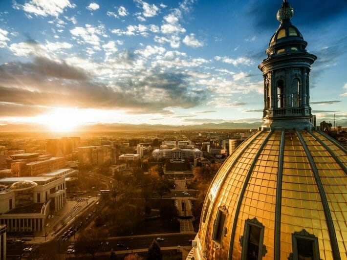 A drone image of the golden dome of the Colorado state capitol building during sunset