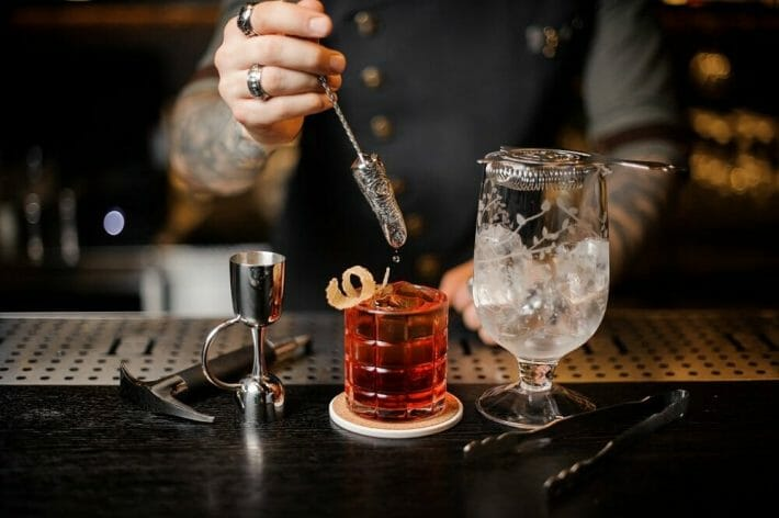 Barman making a classic cocktail using professional bar equipment on the counter