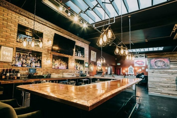 A modern prohibition era-styled bar with warm lighting, bottles, and artwork