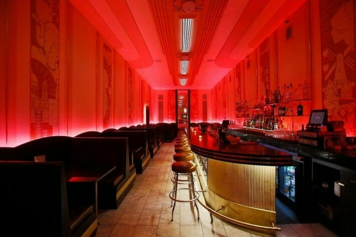 A long and narrow bar with hot pink lighting and dark black booths at the Cruise room, one of the best Denver speakeasies