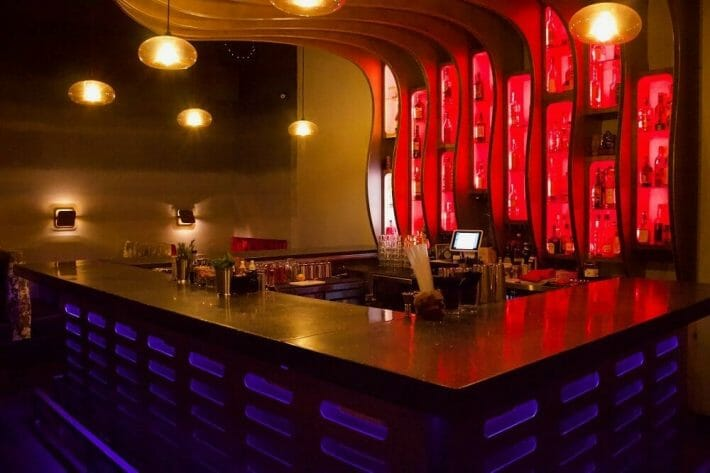 A square bar with deep red lighting behind it and blue lighting below it