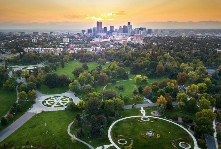 An aerial, sunset view of downtown Denver with green city park and trees in the foreground