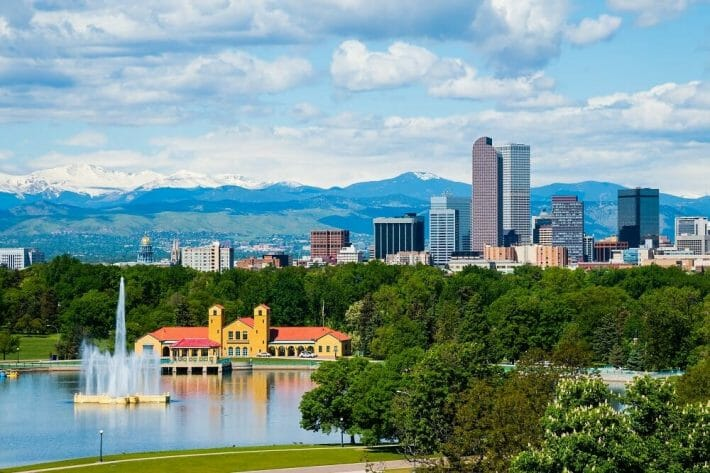 The lake and trees of City Park with downtown Denver and snowy mountain tops in the background