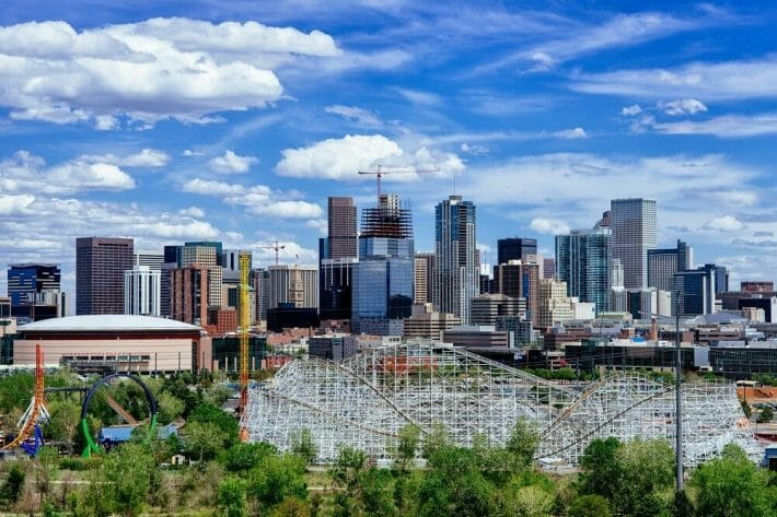 Denver, CO skyline during the day; rollercoaster in the foreground and blue but cloudy skies