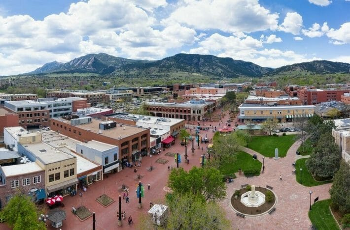 An aerial view of Boulder's famous Pearl Street Mall; blue, cloudy sky and mountains in the background