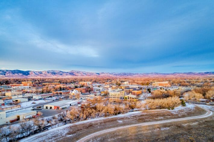 colorful photo of downtown fort collins colorado; buildings, snowy trees, and mountains in the background
