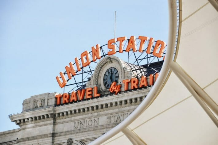 """An orange sign """"UNION STATION TRAVEL by TRAIN"""" tops a limestone building"""