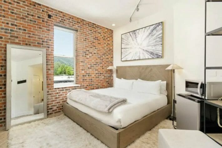 bedroom with one exposed brick wall, large mirror and white bedding