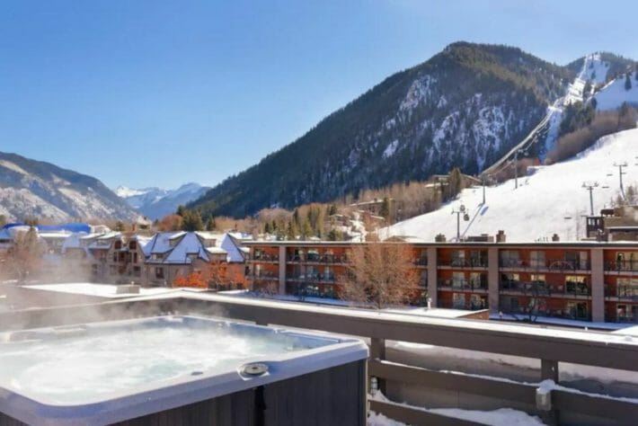 steaming outdoor hot tub with snowy mountain ski slopes in the background