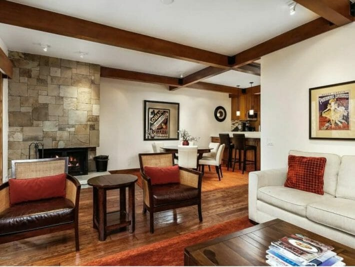 living room featuring wood accents, white couch and leather chairs; partial view into dining room