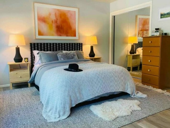bedroom with mirrored closet doors, blue bedding and artwork above the bed