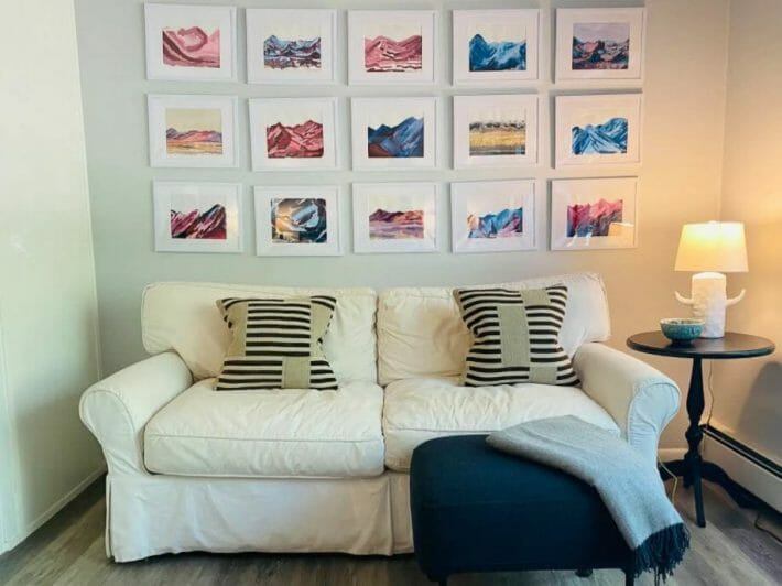 white living room sofa with many pieces of artwork hung neatly above