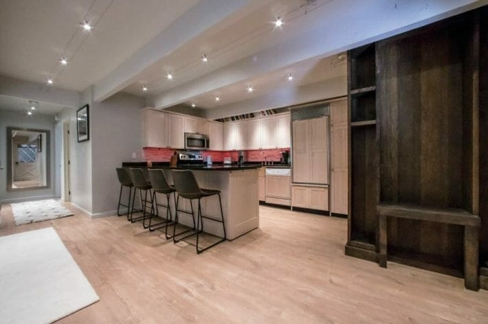 view into the kitchen with barstool seating at the counter, twinkling recessed lighting in the ceiling