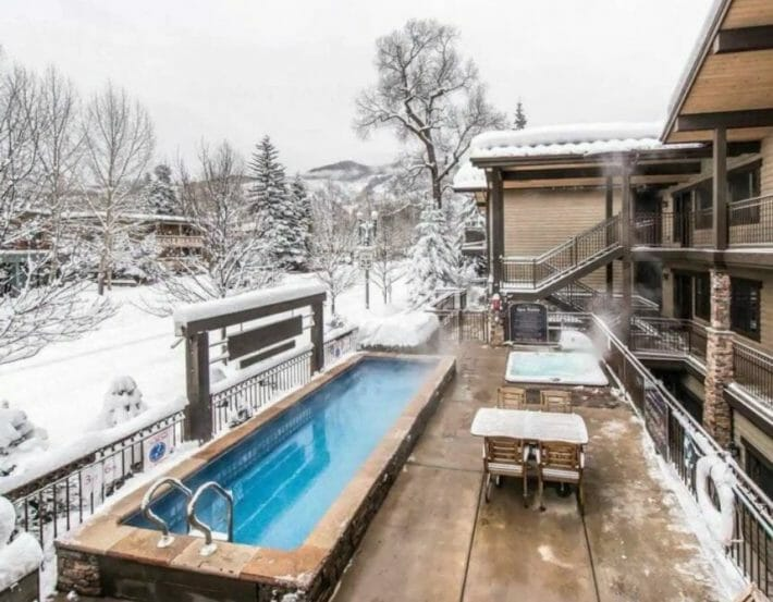 A long, blue outdoor pool with snow covering the deck and trees nearby