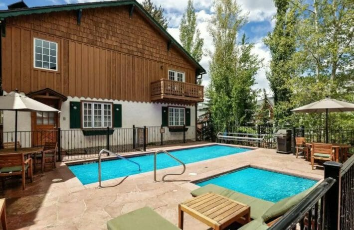 building with wooden siding, next to bright blue swimming pool and hot tub