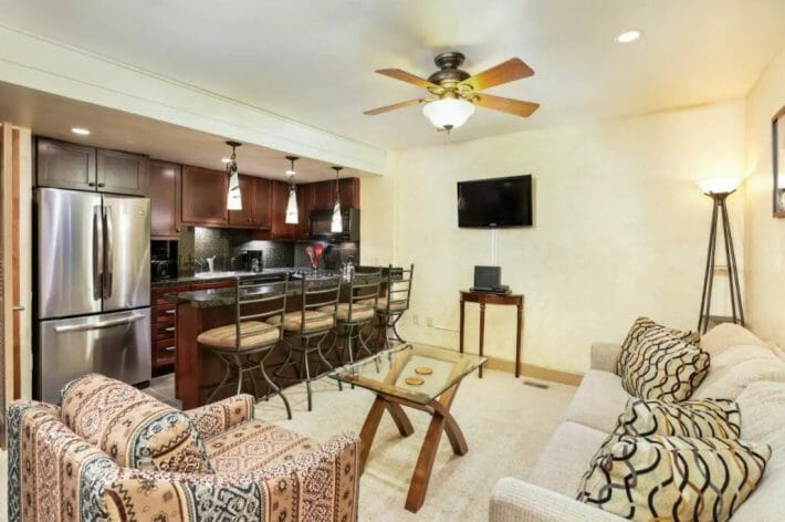 A comfortable living room/kitchen combo with dated furniture but modern kitchen