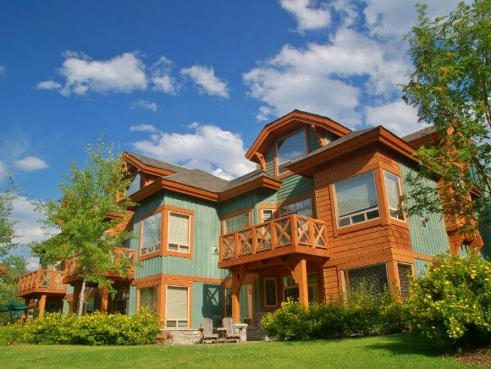 Large green and wood ski condo building, blue skies, green grass and flowers