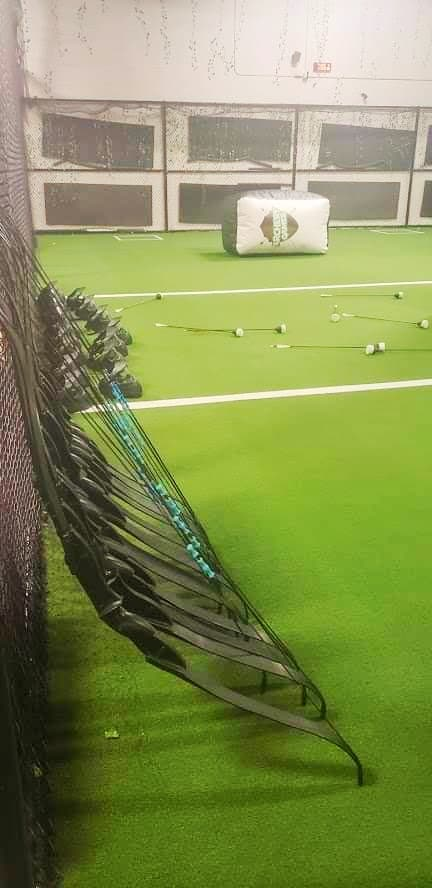 Green playing field at Archery Games Denver with bows and helmets lined up along the left fence