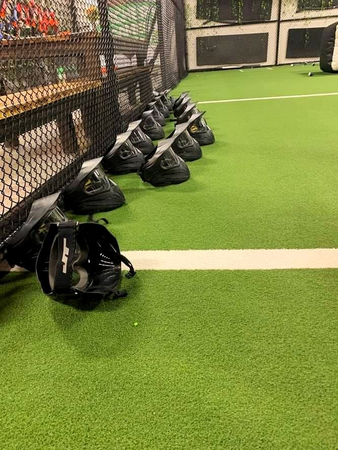 Black helmets lined up along a black chain-link fence on a green field with white lines