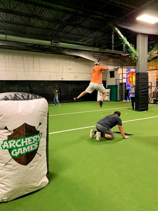 """An obstacle with """"archery games Denver"""" in the foreground; one player crouching on the field with another shooting mid-air"""