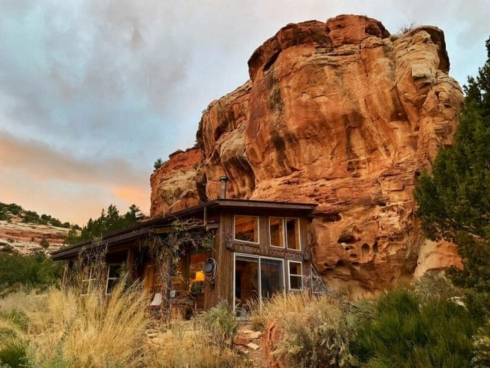 A brown sided house built into the side of a towering red cliff