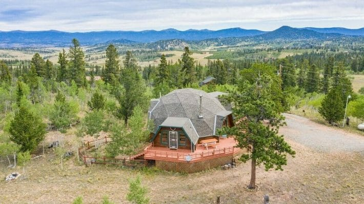 A hexagon shaped home sits among many green trees; mountains in the background