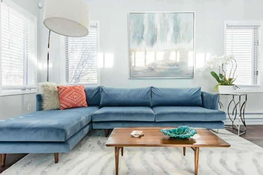 Living room with light gray walls and a large, blue velvet sectional sofa
