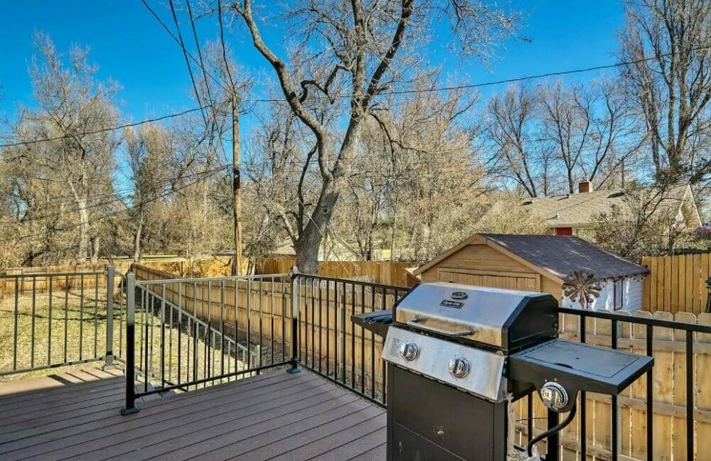 backyard deck with railing and BBQ grill; view into backyard