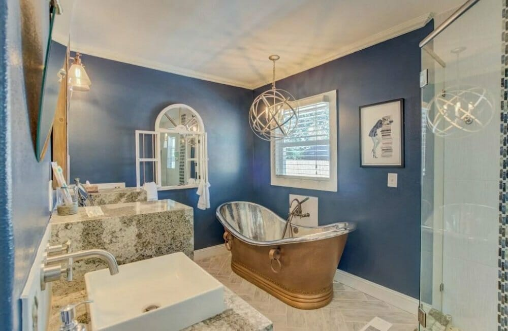 A luxurious bathroom with blue walls, a copper soaking tub and a chandelier hanging above the tub