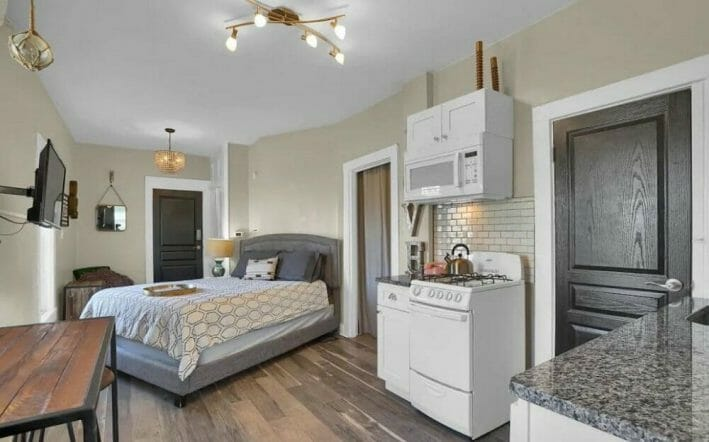 A small, one room studio fits a queen sized bed and a kitchenette