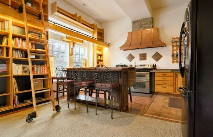 A luxurious kitchen next to the library - tall shelves filled with books and a rolling ladder