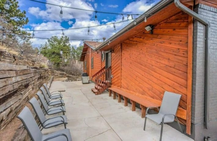 A large patio/concrete pad behind a red wood house; chairs for seating and overhead string lights